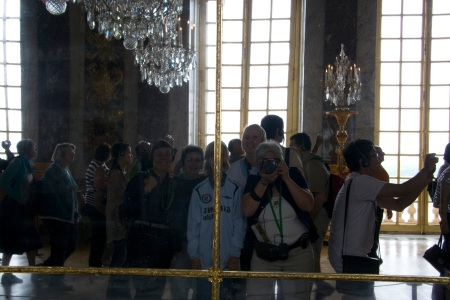 E.g. shoots herself, and the rest of us, in Versailles' Hall of Mirrors